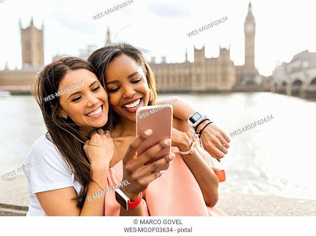 UK, London, two happy women with smartphone near Westminster Bridge