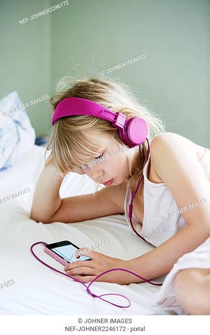 Girl with headphones using cell phone