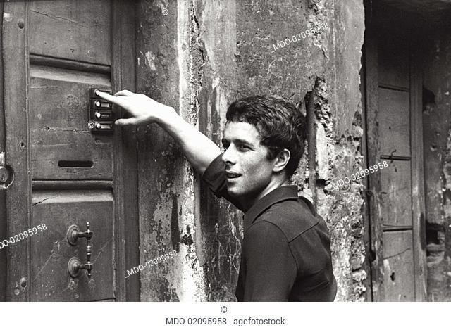 Italian actor Gabriele Lavia calling on the entryphone of a door. Rome, 1970s
