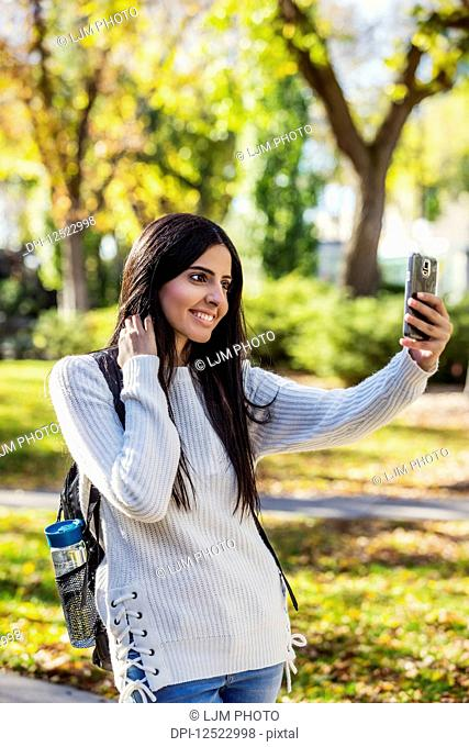 A young female university student of Lebanese ethnicity poses for a self-portrait using her smart phone; Edmonton, Alberta, Canada