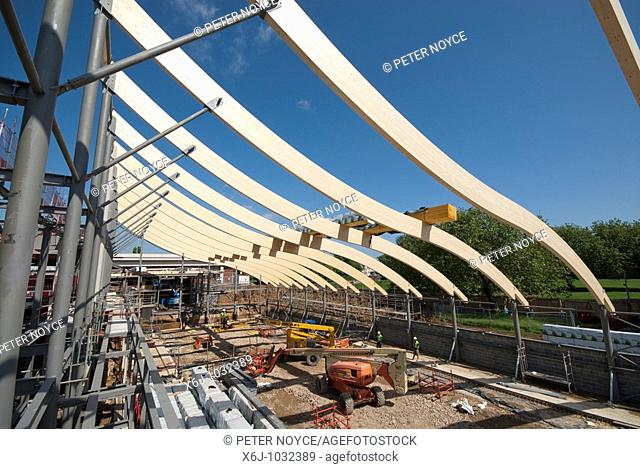 High level Construction workers building laminated wood wave roof on Mountbatten centre in Portsmouth