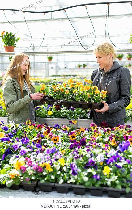 Mother with daughter choosing flowers in garden center