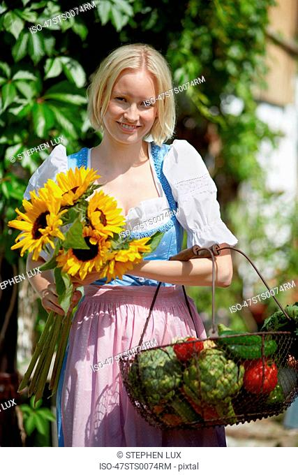 Woman picking flowers and vegetables
