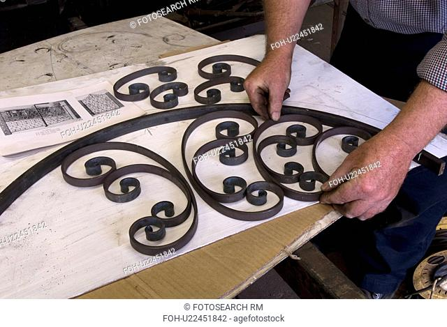 Blacksmith preparing curved top of gate and placing crafted metal scrolls in frame to check for accuracy prior to assembly