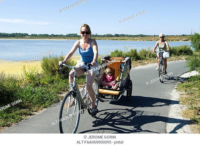 Multi-generation family enjoying bicycle ride, children sitting in bicycle trailer
