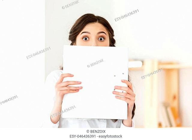 Young woman with surprised eyes peeking out from behind paper poster. Businesswoman holding big white banner in modern office