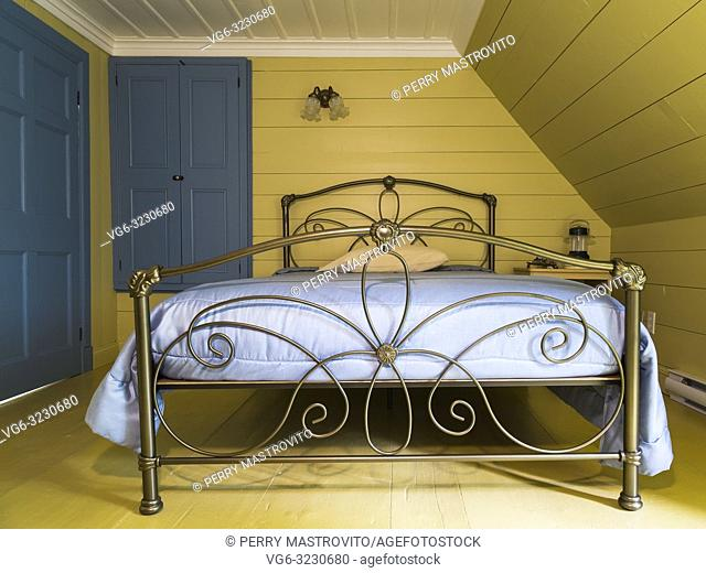 Double bed with antique brass metal headboard and footboard in upstairs master bedroom inside an old 1809 French regime cottage style home