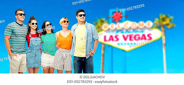 entertainment, leisure and friendship concept - group of happy smiling friends in sunglasses hugging over welcome to fabulous las vegas sign background
