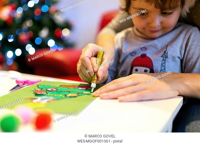 Mother helping her little daughter tinkering Christmas decoration