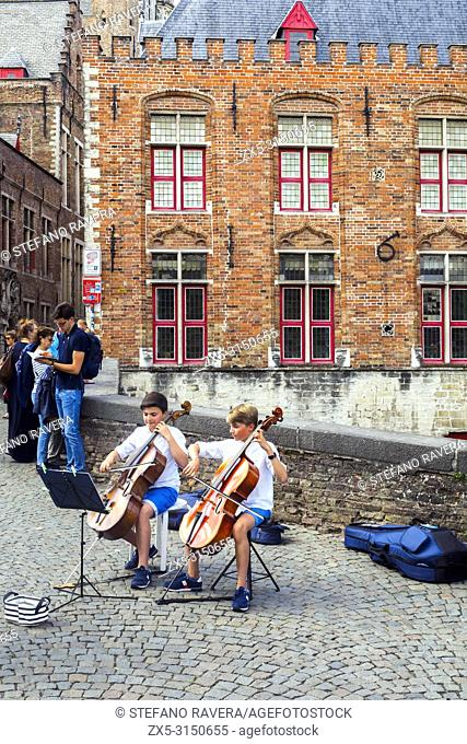 Two young musicians playing cello in the historic center - Bruges, Belgium