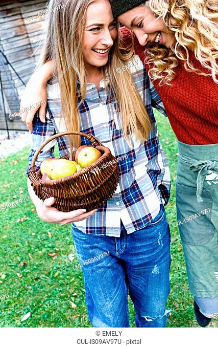 Two friends with arms round each other, one carrying basket of apples