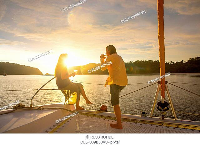 Couple relaxing on yacht at sunset, Koh Rok Noi, Thailand, Asia