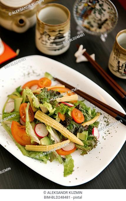 Chopsticks on plate of salad