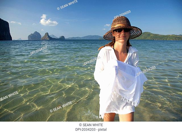 A Woman Tourist Walks In Shallow Clear Water On A Sand Island Near El Nido And Corong Corong, Bacuit Archipelago Palawan Philippines