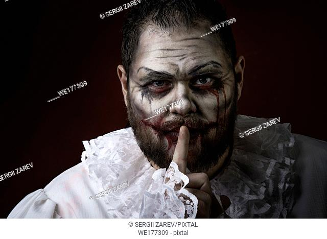 Portrait of a Scary Evil Clown. Studio shot with horrible face art