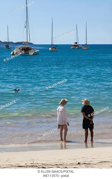 Man and woman in matching hats wading in the water on the beach with sailboats moored off shore
