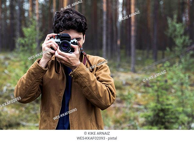 Finland, Lapland, man taking picture in rural landscape
