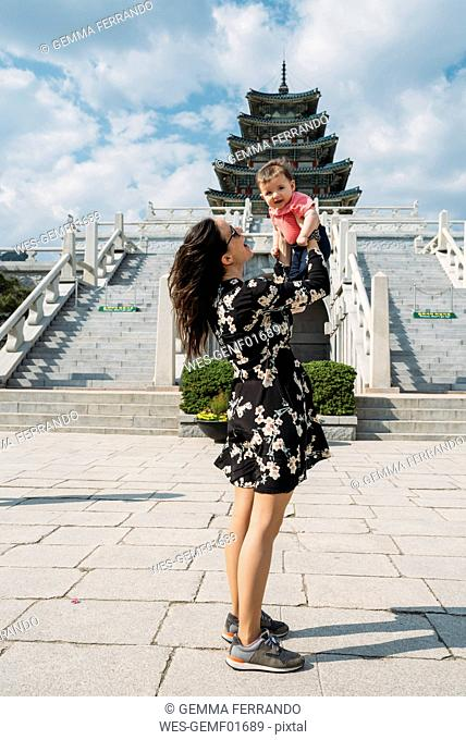 South Korea, Seoul, woman holding a baby girl in front of the National Folk Museum of Korea, inside Gyeongbokgung Palace