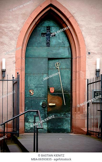 The heavy iron door of the entrance of the St. Stephan church in Mainz with engraved Latin words