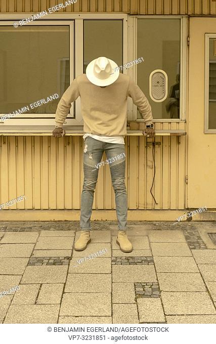 streetstyle, stylish man hiding face under hat, Munich, Germany