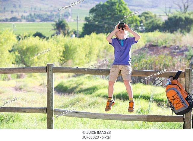 Boy sitting on fence looking through binoculars