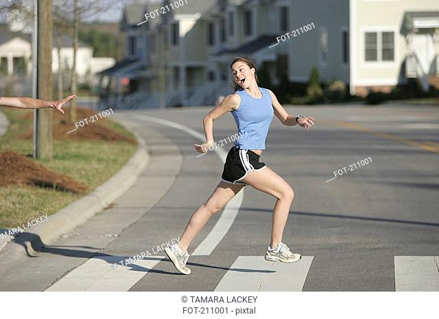 Young woman looking over shoulder while jogging across road