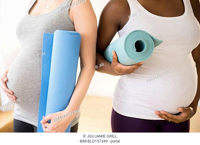 Pregnant women carrying yoga mats