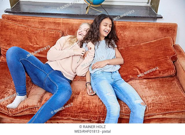 Two laughing girls relaxing on couch