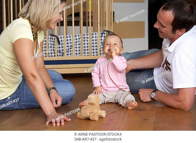 Parents playing with baby, Engen, Baden-Wuerttemberg, Germany