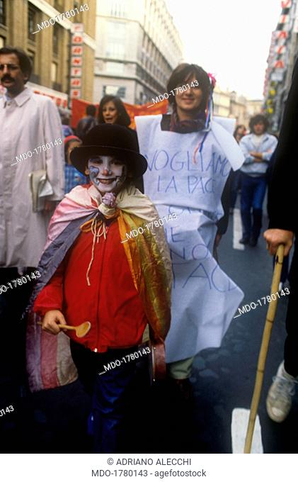 A boy dressed up as a clown at a peace demonstration. A boy dressed as a clown with a peace flag as a cape attending a peace demonstration