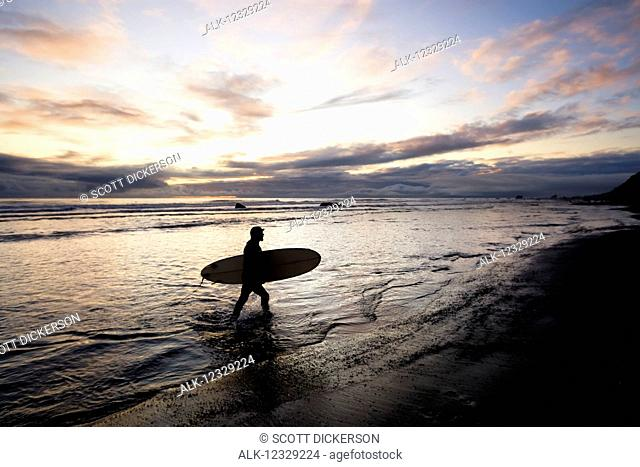 Silhouette Of A Surfer Carrying A Surfboard Back To Shore At Sunset; Alaska, United States Of America