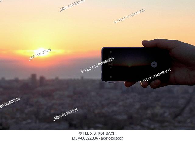 Hand with smartphone photographing the sunrise over Barcelona
