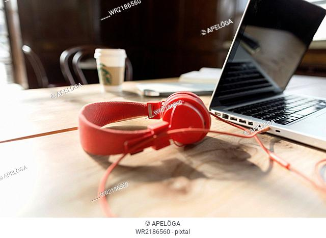 Close-up of red headphones and laptop on table in cafe