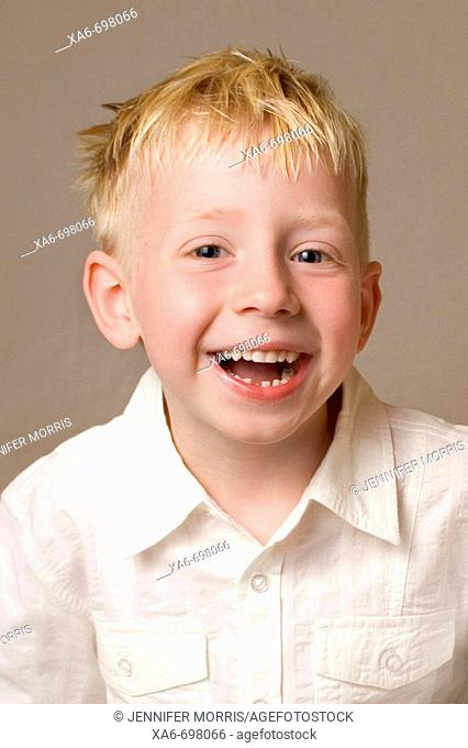 A five-year-old blonde-haired, blue eyed boy is laughing and looking straight at the camera. He is wearing a white shirt and one of his teeth is missing
