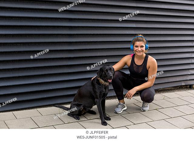 Portrait of smiling young woman with headphones and her dog outdoors