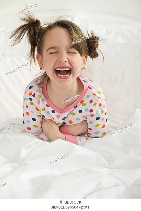Laughing Caucasian girl sitting in bed