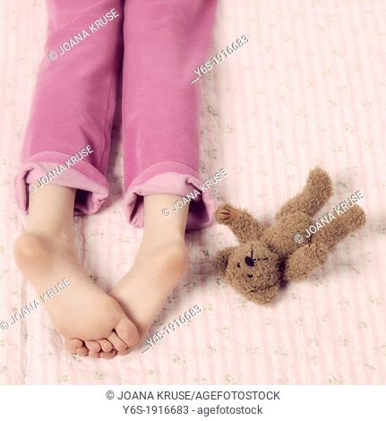 female feet in pink pyjamas with a teddy bear