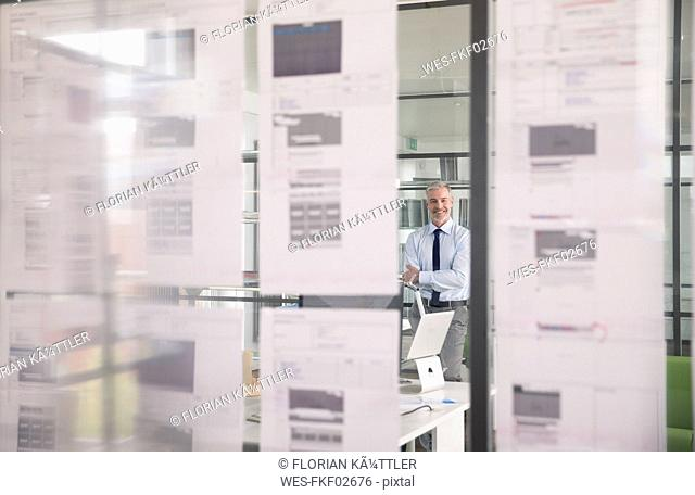 Businessman standing in office, drinking office