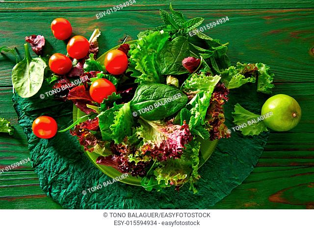 Green salad with spinach lettuce tomatoes feta cheese on monochrome wood