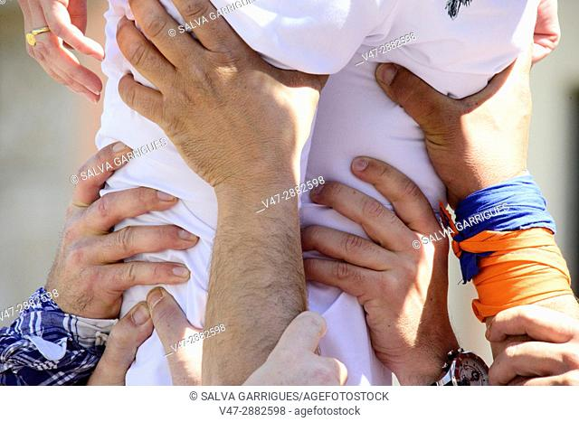 Many hands hold the legs of a person to perform the castle (Castell), Valencia, Spain