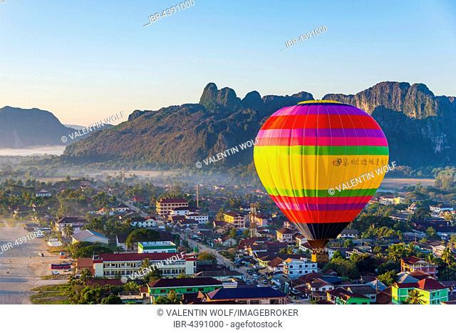 Colorful hot air balloon drifts over the city, karst mountains behind, Cityscape, Vang Vieng, Vientiane Province, Laos