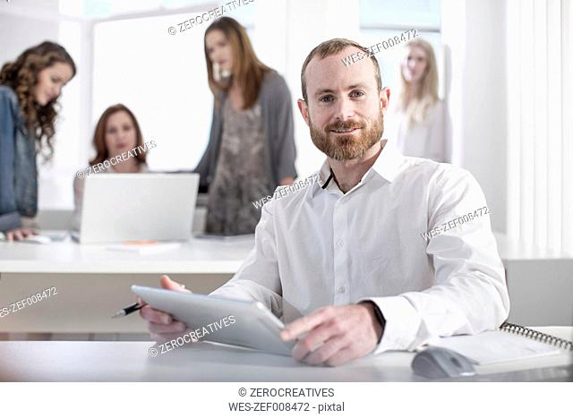 Portrait of confident man with digital tablet in office
