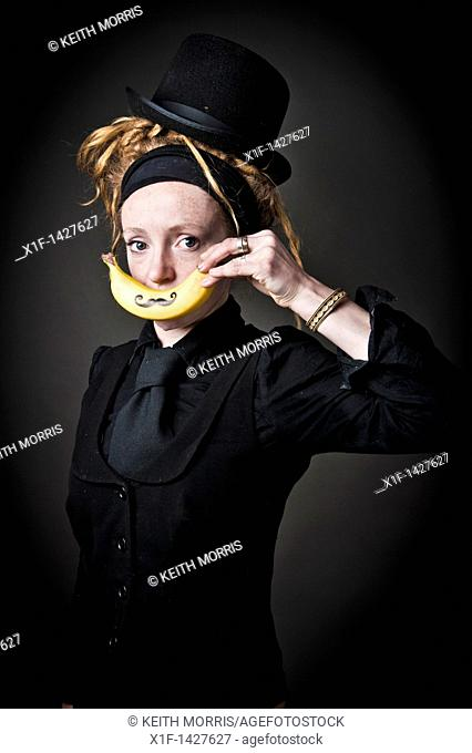 Young alt punky funky woman holding a banana with a moustache drawn on it over her mouth