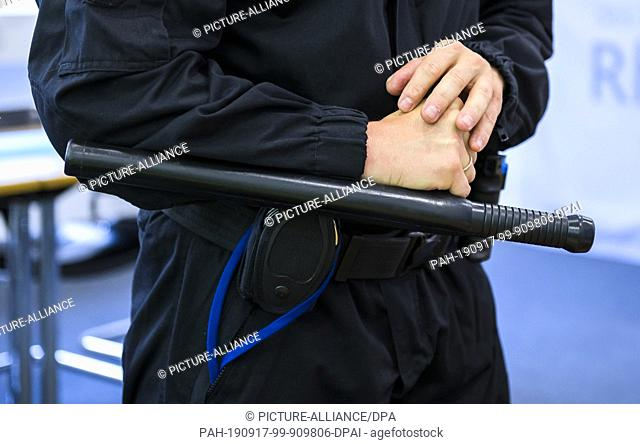 16 September 2019, Rhineland-Palatinate, Mainz: At a press conference at the Ministry of Justice, John Klein, prison officer, holds the new baton