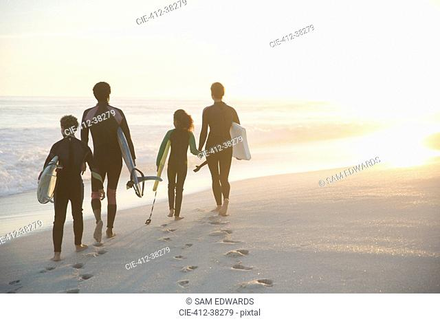 Family in wet suits walking with surfboards on sunny summer sunset beach