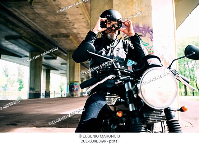 Mature male motorcyclist sitting on motorcycle putting on goggles under flyover