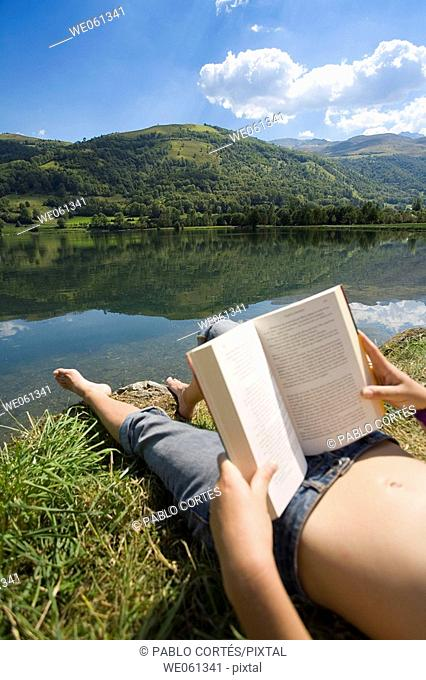 Young woman reading by lake with Pyrenees Mountains in background