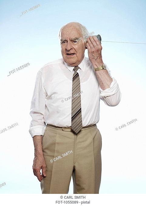 Senior man comically strains to listen on tin can phone