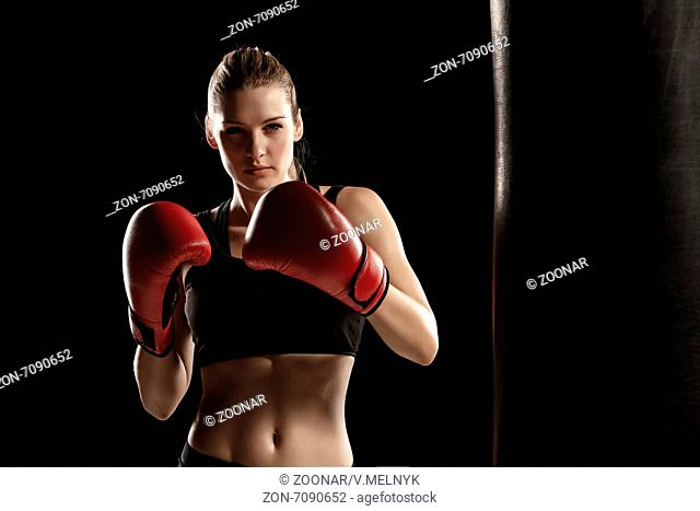 beautiful woman is boxing on black background