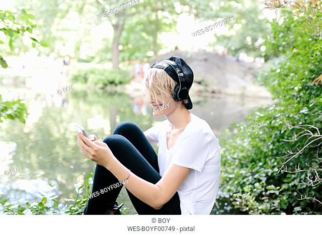 Young woman sitting at lakeside in park wearing headphones and looking at cell phone